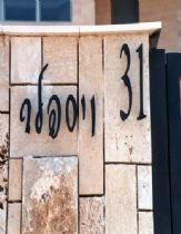 An exterior sign for a house from iron letters on a stone wall