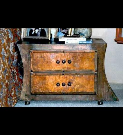 A chest of drawers made of metalworked iron and a hammered copper concealment